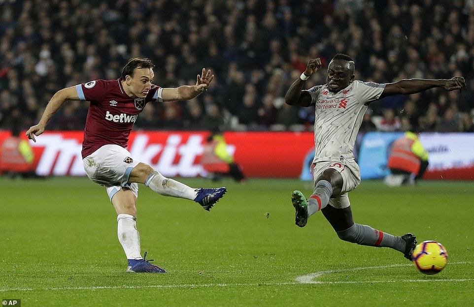 Mark Noble attempted a shot on goal under pressure from goalscorer Mane but his effort did not trouble Alisson in goal