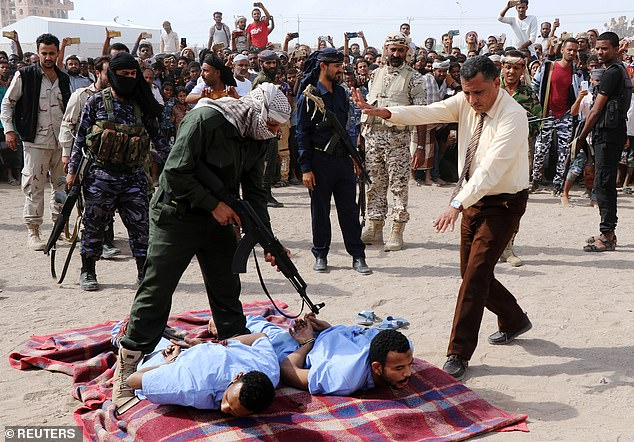 Eye for an eye: A local doctor, right, makes a final check before the execution of Wadah Refat, 28, and Mohamed Khaled, 31, who were convicted of raping and murdering a 12-year-old boy