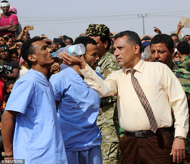 Dr. Salah Mohamed Hussein, director of a local Forensic Unit, gives water to  Khaled before their execution