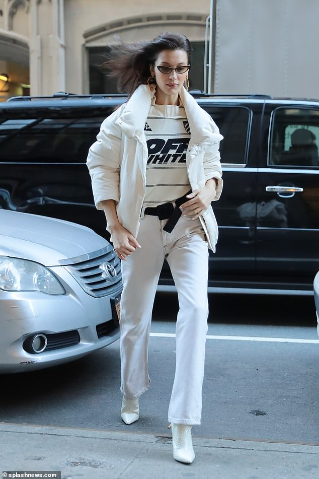 City style! Bella Hadid put on a traffic-stopping display in a white puffy jacket and flared jeans as she strolled across the street in New York on Saturday