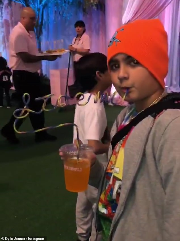 Sip it up and start again: Cousin Mason sipped on an orange soda from a curly Stormi straw