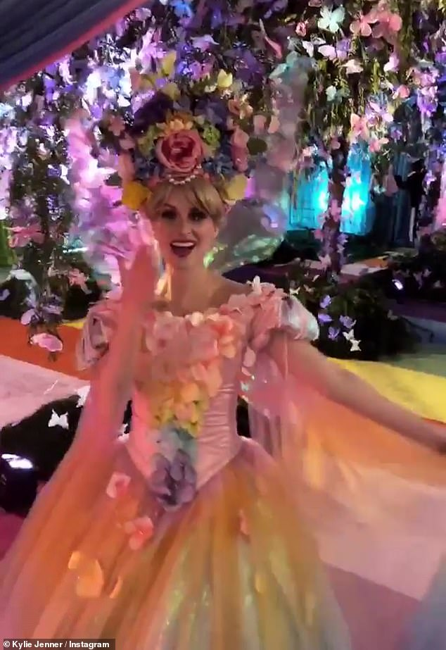 """Enchanting: the princesses with beautiful wreaths of flowers welcomed the people in a """"rainbow butterfly forest"""" with colored plants falling from the ceiling"""