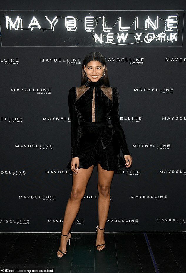 Megawatt smile: Danielle Herrington arrived in a black full-sleeved mini-dress with a turtleneck and some sheer strips of fabric around the decolletage area