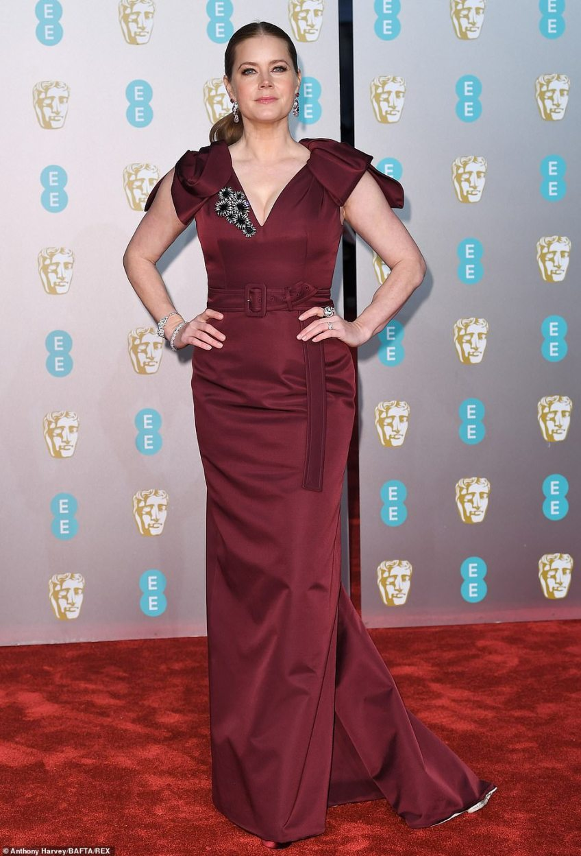 Centre stage: The star, who is up for Best Actress in a Supporting Role for her role in Vice, dazzled in the low-cut number which was lined with an embellished brooch and put focus on her sensational front
