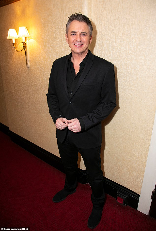 Dapper:After the performance, Shane switched into a sleek black suit, teamed with coordinating shirt and shoes, to enjoy the after-party