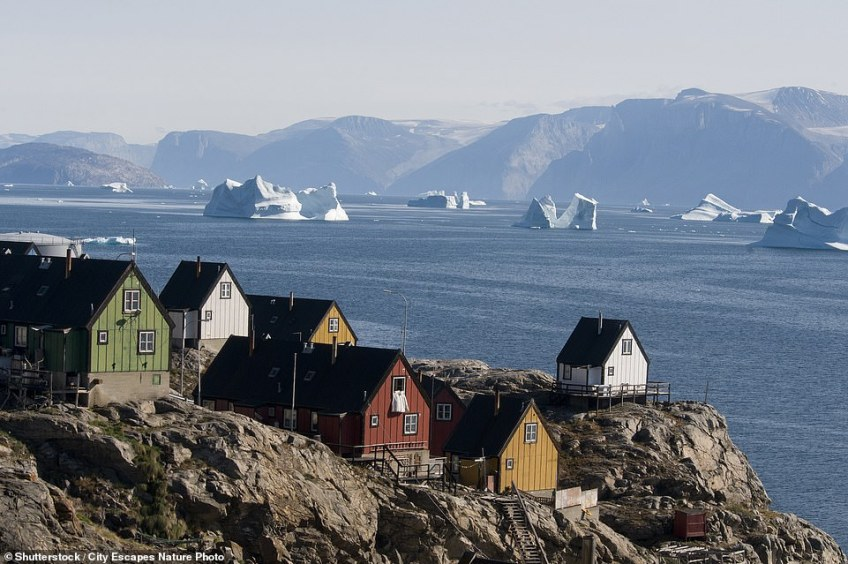 Pictured are houses in Uummannaq overlooking an iceberg-laden bay