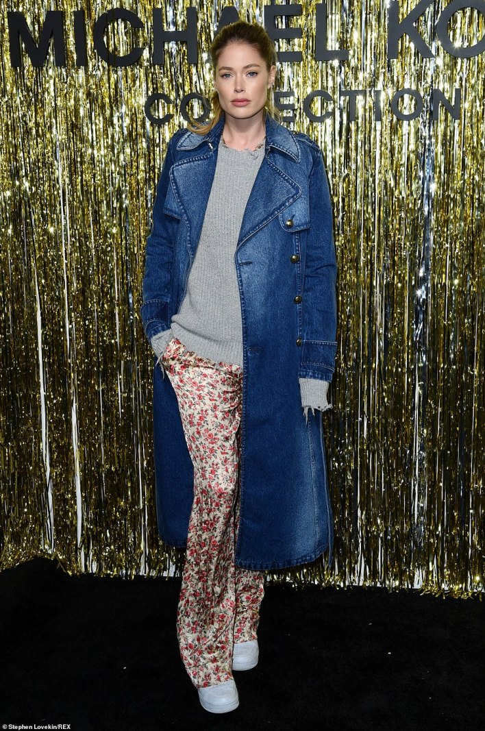 Delightful in denim: Model Doutzen Kroes sported a long denim coat over a grey knit sweater, floral patterned trousers, and white sneakers