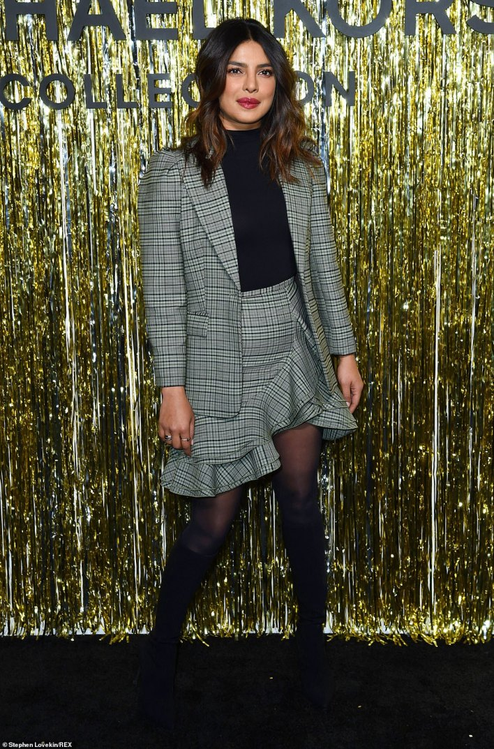 Dark side:She contrasted the patterned combination with a black top with matching stockings and knee-high suede booties