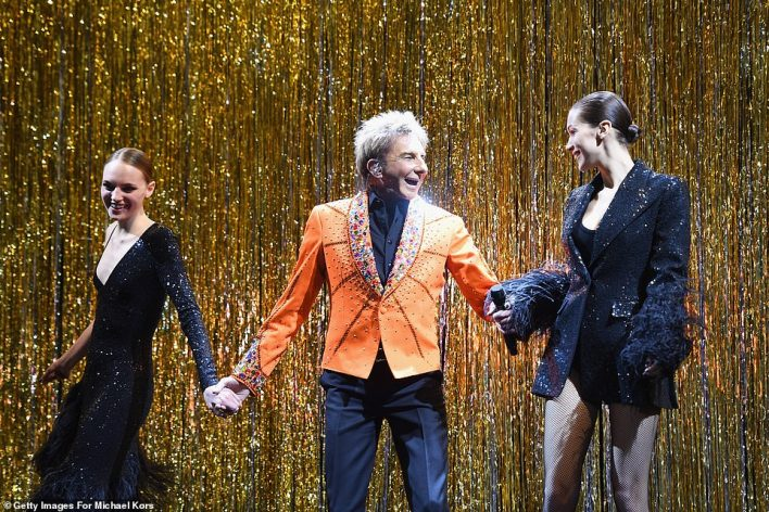 Shining star:The 75-year-old singer sported a bright orange blazer featuring studs and colorful jewels fastened to the lapel and sleeves as he performed the Copacabana