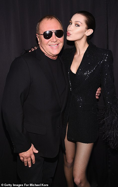 Proud: Bella hugged the American fashion designer and even puckered her lips by him