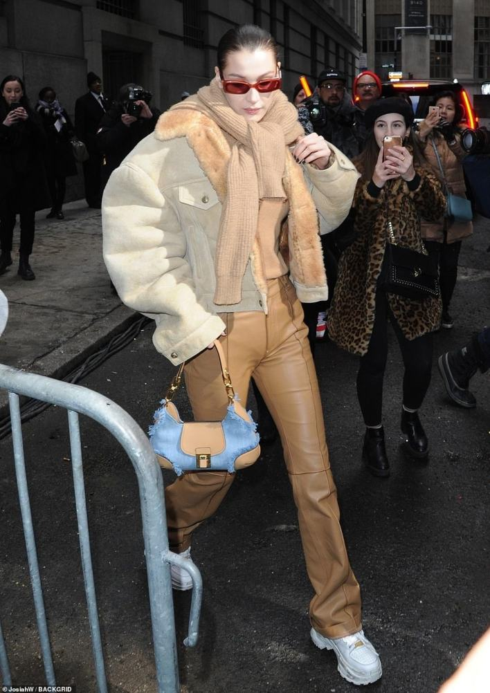 Moving on:Bella looked very fashionable in an oversized beige jacket over a camel-colored cashmere sweater tucked into light brown leather pants and white leather designer sneakers