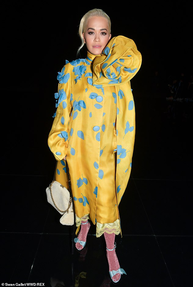 Making a statement:Rita Ora arrived in a subtle ensemble of bright yellow couture wrap coat with bright blue flowers as part of the design