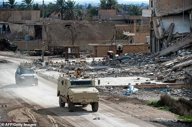 Vehicles belonging to the US-led coalition drive along a road on Sunday in the Syrian village of Baghouz on the front line
