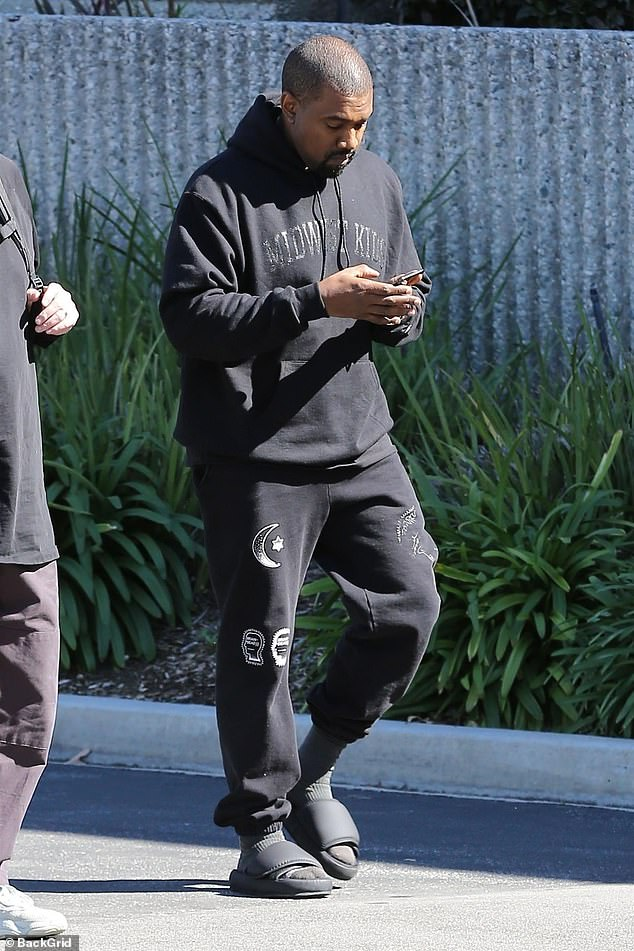 Checking his phone: the 41-year-old rapper wore a black hooded Midwest Kings sweatshirt, black sweatpants and a pair of slippers as he was seen while checking his phone