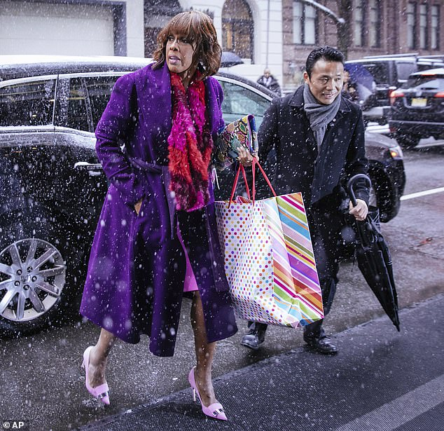 Dressing for the part: Gayle King arrived in a bright pink pink dress and pastel-colored heels while carrying a colorful gift bag that featured fuchsia stripes and polka dots