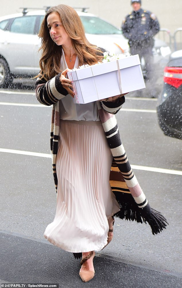 Party people: One woman donned a light pink skirt that matched the ribbon on the box she was carrying into the party