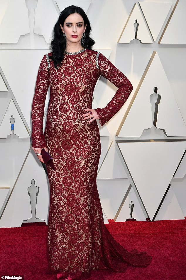 Lady in red: The Breaking Bad actress' burgundy gown hugged her growing bump while cascading down to the floor with a modest sweep train