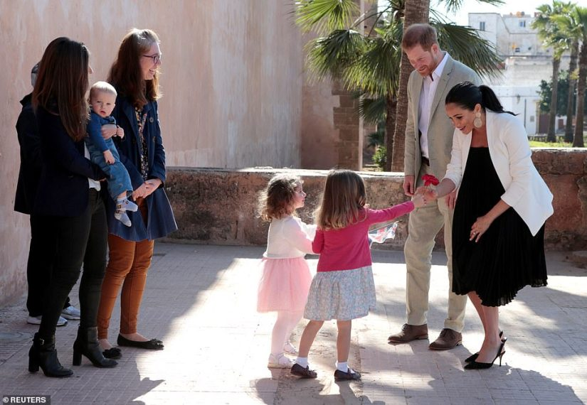 Later, on a visit to the Andalusian Gardens in Rabat, Meghan wore a more formal outfit. The couple were welcomed to the gardens by three-year-old Imogen and Tabitha who presented a delighted Meghan with a rose upon her arrival