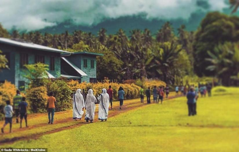 The church complex includes a church made out of breeze blocks, a parish hall, a grassy field for events, a house for the nuns and another for Father Ralph. Above, three nuns make their way back home after a service