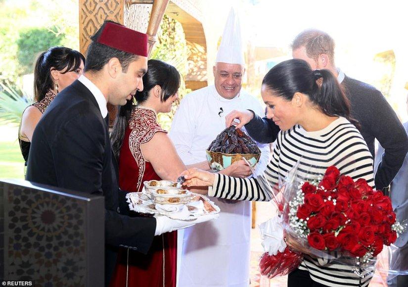 Meghan could be seen sampling dates after she was presented with an enormous bunch of red roses