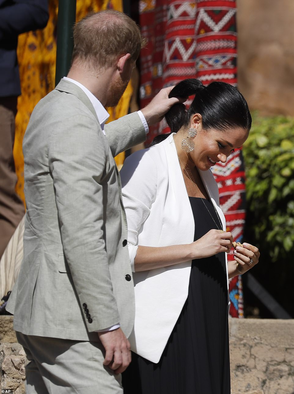 Ever the attentive husband, Prince Harry could be seen assisting Meghan with her ponytail as the local man placed it around her neck