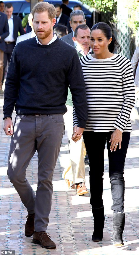 Meghan wore a cool Breton style top with black jeans and black Stuart Weitzman ankle boots for her morning engagements