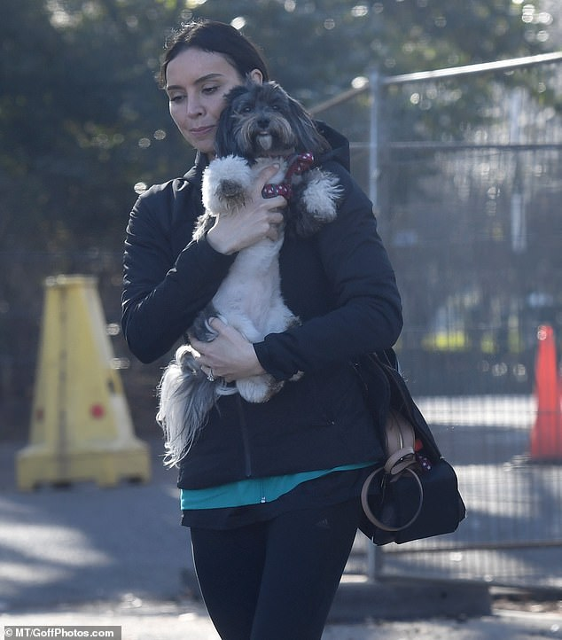 Doting: Christine gave her pooch Minnie the most of her attention as she carried the pup and bestowed on her plenty of cuddles