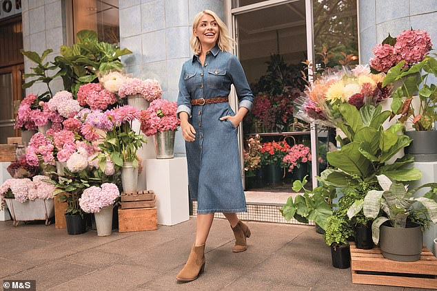 Holly's Must Haves Denim Edit includes two dresses in different lengths. Pictured, the TV star in the midi shirt dress, £49.50; leather buckle hip belt, £19.50; suede ankle boots, £49.50