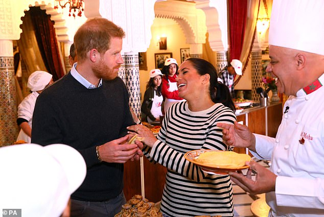 The Duke and Duchess of Sussex share a light-hearted moment during a cooking demonstration in Rabat. The British Ambassador was impressed by the 'spontaneous' couple