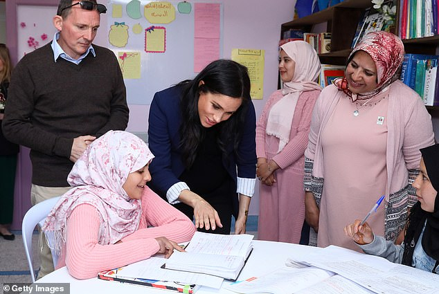 The Duchess of Sussex, accompanied by British Ambassador Thomas Reilly (left), looks at the work being done by girls at the 'Education For All' boarding house in Ansi on Sunday
