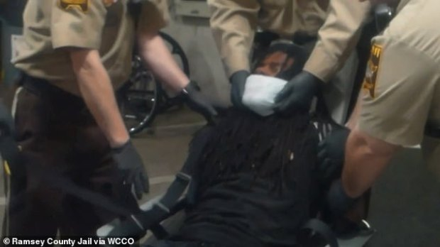 The footage shows Johnson being manhandled and a spit-guard mask his placed on his face