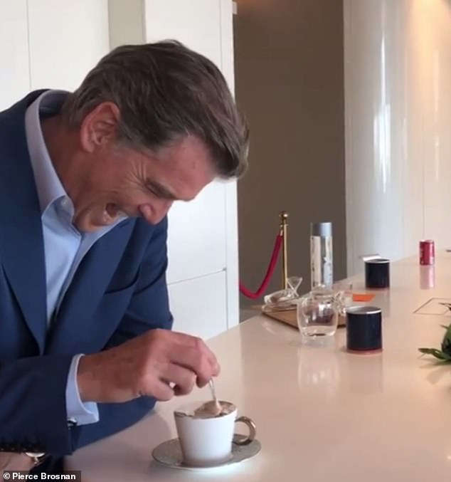 Handsome: Looking as dashing as ever in a navy suit and baby blue shirt, Pierce looked in his element as he enjoyed the warm personalised beverage