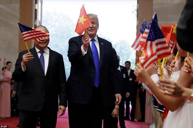President Donald Trump waves a Vietnam flag as he meets with Vietnamese Prime Minister Nguyen Xuan Phuc, waving an American flag