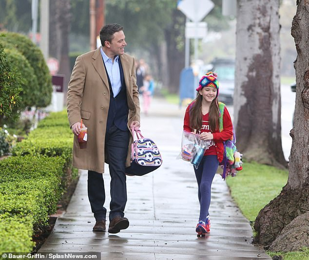 Wet weather: Ben and Seraphina shared a laugh as they made their way through the drizzle