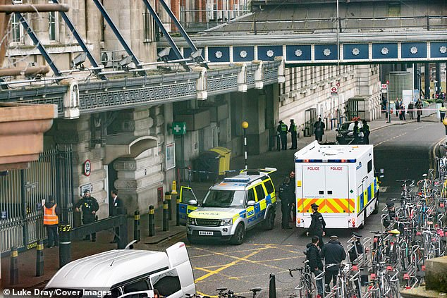 Security alert: Two police vehicles and several officers at the scene at London Waterloo station on Tuesday after one of the explosives was found at the country's busiest rail terminal