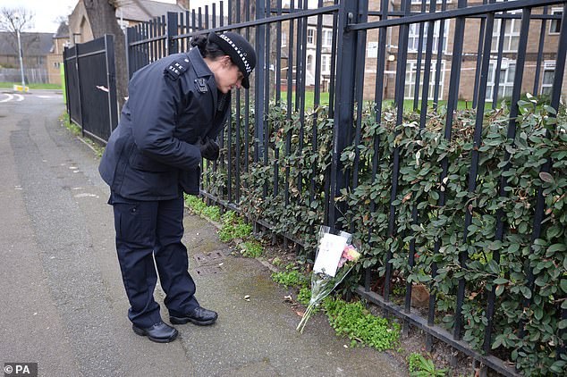 A police officer inspects one of the floral tributes left for the stabbing victim in Leyton today