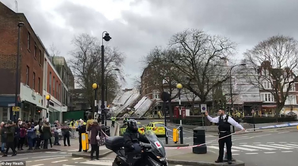 A large group of people are gathered behind a large cordon after the collapse of the scaffolding in London today