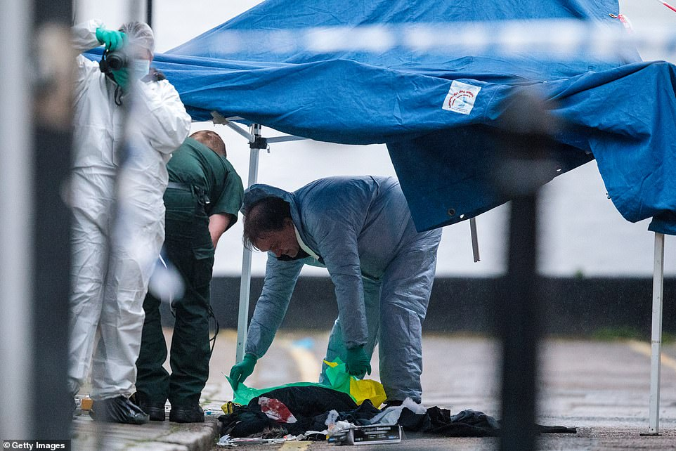Bloodied garments are seen as forensic teams work at the scene of a stabbing in West Kensington on yesterday afternoon