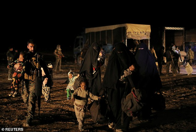 Women walking with belongings and their children as an SDF fighter helps them, near the village of Baghouz, Deir Al Zor province, in Syria yesterday