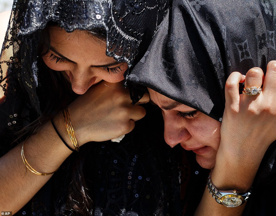 Sara Baluch, left, mourns with Lilly Sharifi while visiting the grave of Baluch's fiance, Mohammad Sharifi