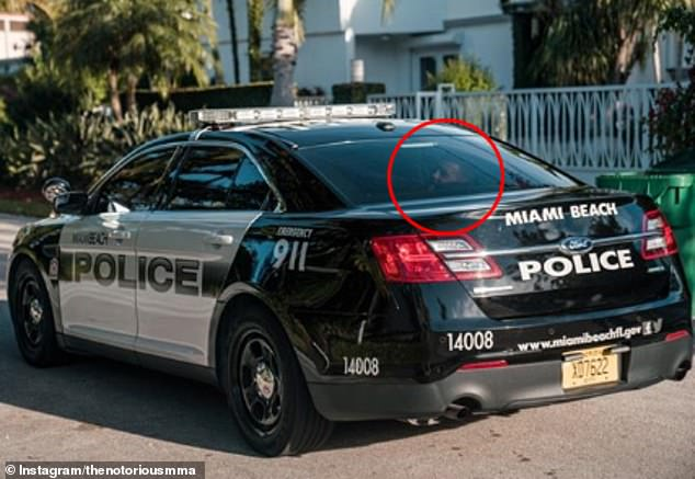 Defiance; Conor McGregor shared a picture of him in the back of a Miami Beach Police cruiser taken after his arrest - and showing him grinning