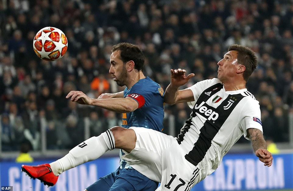 Mario Mandzukic hangs out a leg to try and get the ball under control but Diego Godin is there to cover for Atletico
