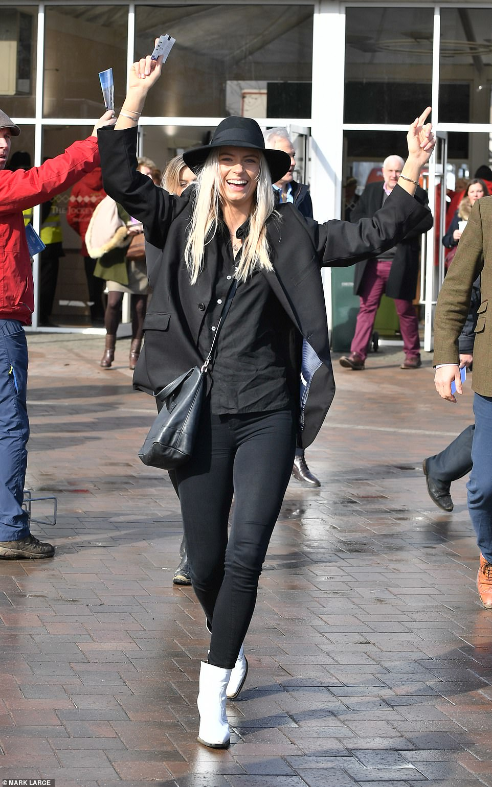Backed a winner? Dressed casually in black jeans, one racegoer was spotted celebrating at the racing action got underway