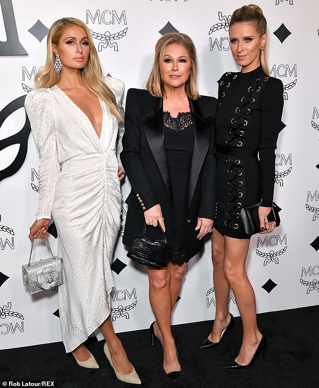 The whole family: Paris Hilton, 38, showed off a timelessly elegant white gown at the newly-christened leather goods store. She was joined by her sister Nicky Hilton, 35, and mother Kathy Hilton, 60, in matching jet black outfits