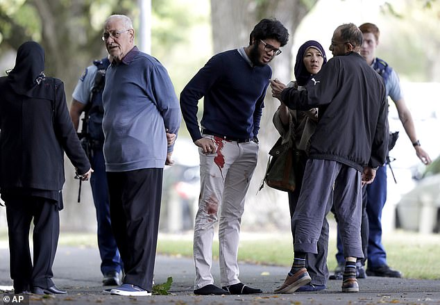 People who survived the attack standing outside the mosque, with some of them still covered in blood