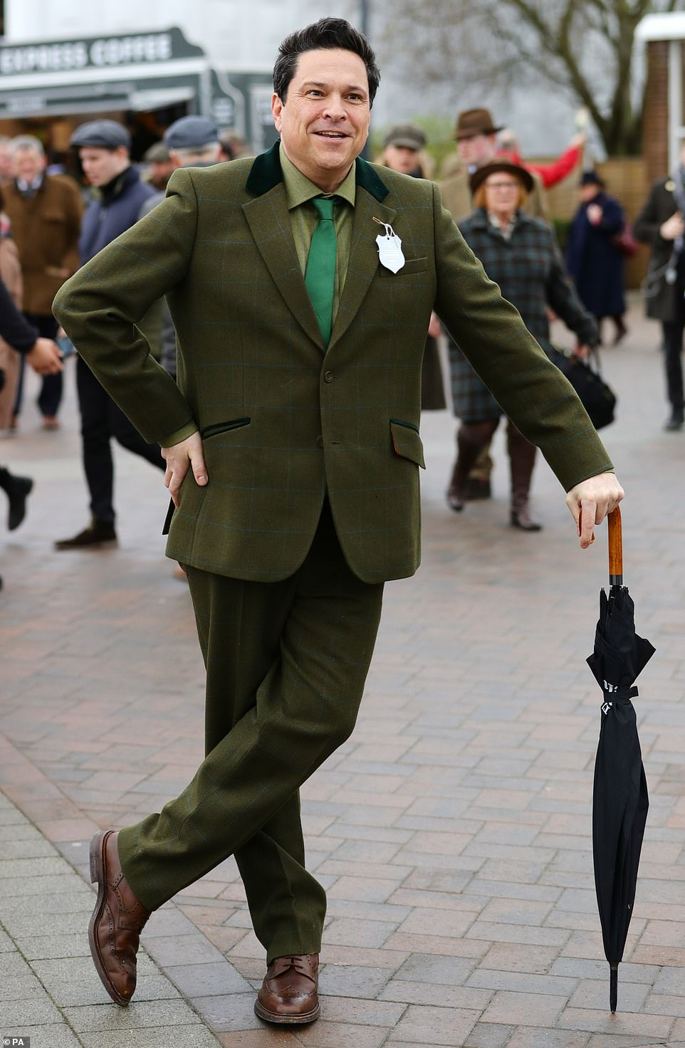 Comedian Dom Joly also came prepared for the wet weather, and donned a smart green tartan check wool suit - a nod to the surrounding Gloucestershire countryside