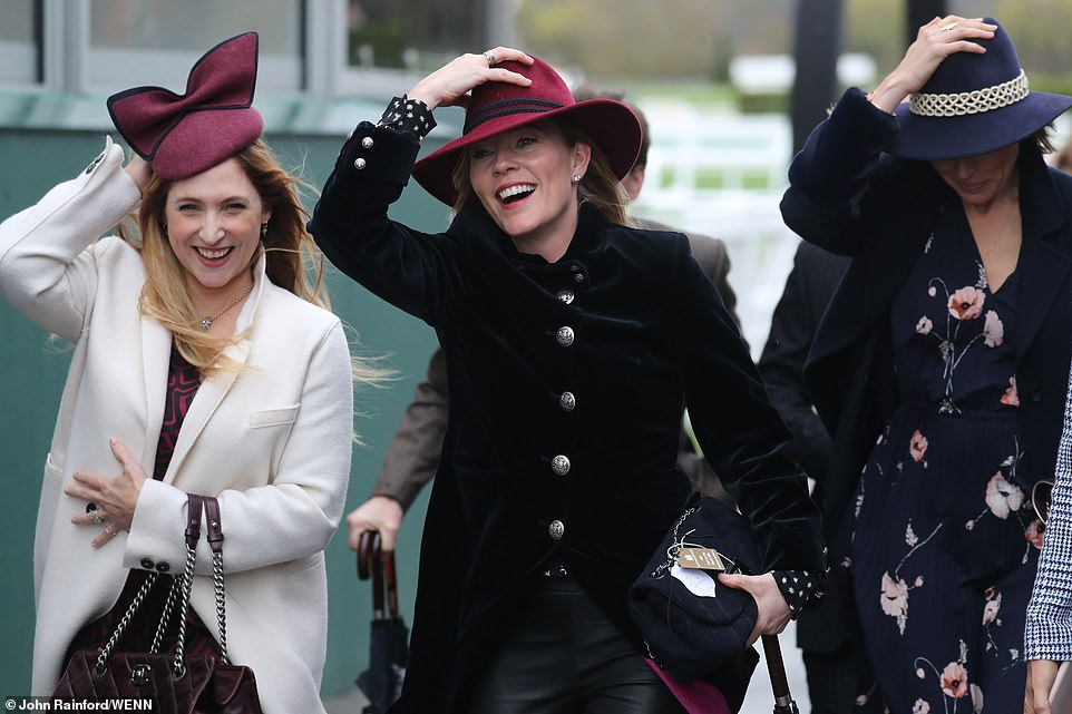 Autumn Phillips (middle) hung onto her Camilla rose fedora hat as she entered the paddock,wearing a navy Guinea London coat