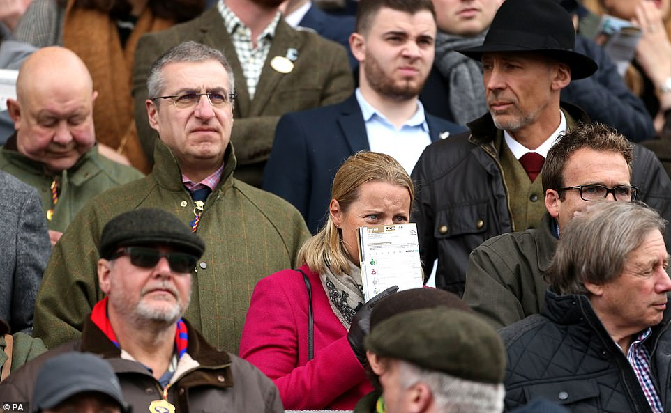 A racegoer can't bring herself to watch the final few hurdles as the action gets underway on Gold Cup Day at Cheltenham