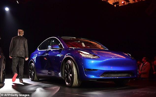 Musk pasa por delante del nuevo Tesla Model Y en su presentación y muestra las suelas rojas de sus zapatillas.