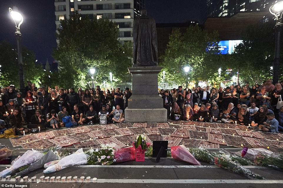 Flowers, candles and prayer mats strewn along the steps of the State Library of Victoria